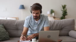 Happy man in headset speaking by webcam looking at laptop