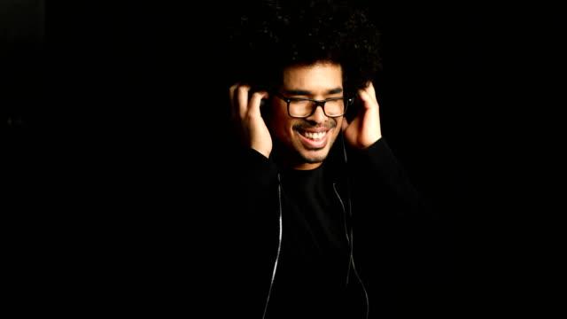 Happy man listening music through headphones