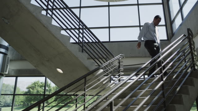 ws ds happy man moving down on office stairs / orem, utah, usa - orem utah stock videos and b-roll footage