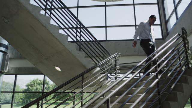 vídeos y material grabado en eventos de stock de ws ds happy man moving down on office stairs / orem, utah, usa - orem
