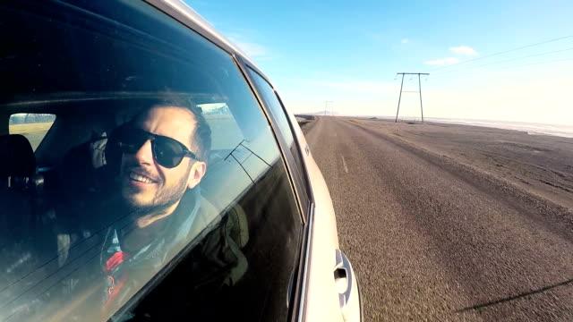 vídeos de stock e filmes b-roll de happy man on a road trip in the car - cantar
