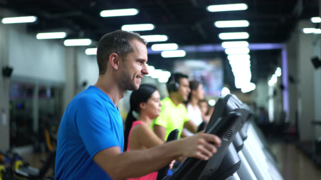 happy man on the elliptical machine at the gym - gym stock videos & royalty-free footage