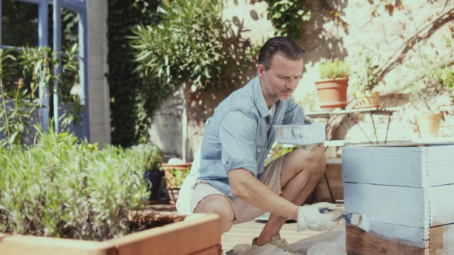 happy man painting diy flower pot outdoor. - modern stock videos & royalty-free footage