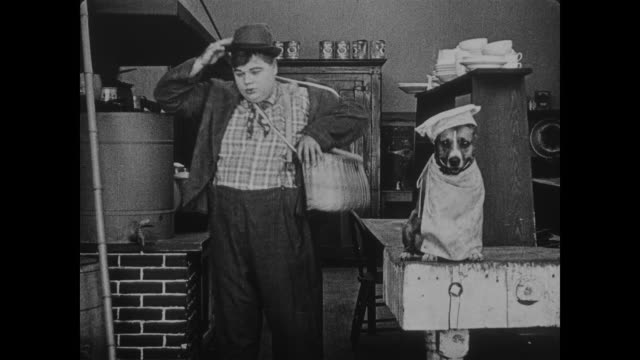 1918 happy man (fatty arbuckle) puts chef's apron and hat on dog before changing into street clothes, leaving kitchen with extra long fishing rod - chef's hat stock videos & royalty-free footage