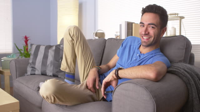 happy man resting on couch - puerto rican ethnicity stock videos & royalty-free footage
