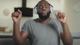 Happy man singing in headphones at kitchen. Male person dancing in headphones.
