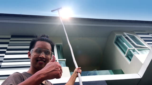 A happy man smiling while wearing protective glasses and sweeping spider web under eaves of modern house against blue sky.