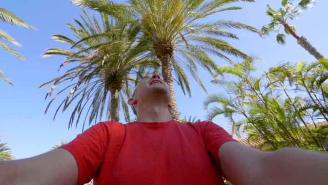Happy man spinning and having fun in tropical resort in slow motion in 4k