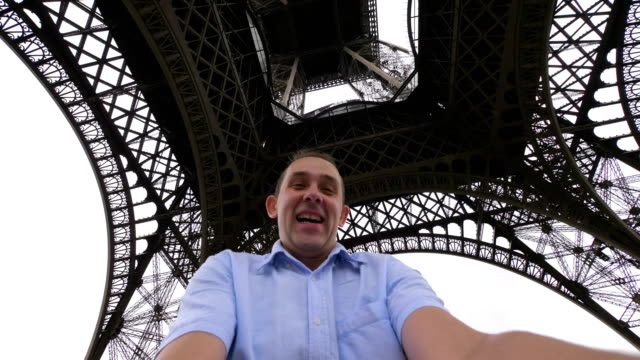 Happy man spinning and having fun under the Eiffel Tower in Paris in slow motion in 4k