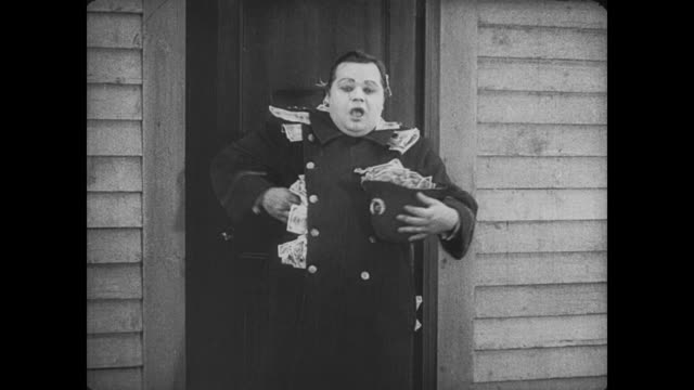 1917 happy man (fatty arbuckle) stuffs money from illegal betting shop inside police uniform until wife appears and drags him home by his ear - fatty arbuckle stock videos and b-roll footage
