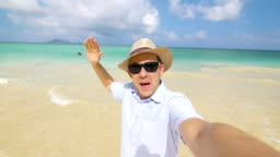 Happy man taking a selfie on Hawaiian beach in 4k slow motion