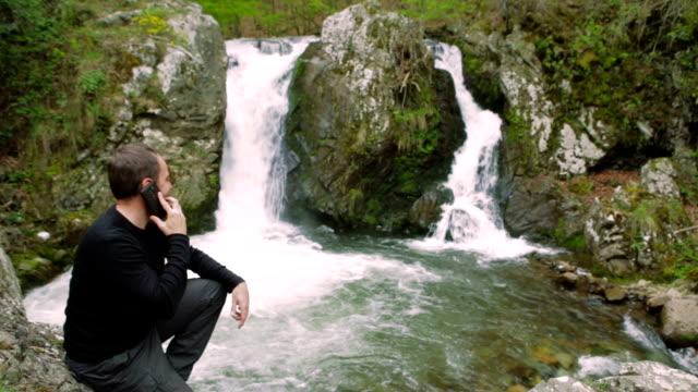 vídeos de stock, filmes e b-roll de homem feliz tirando fotos da cachoeira - árvore de folha caduca