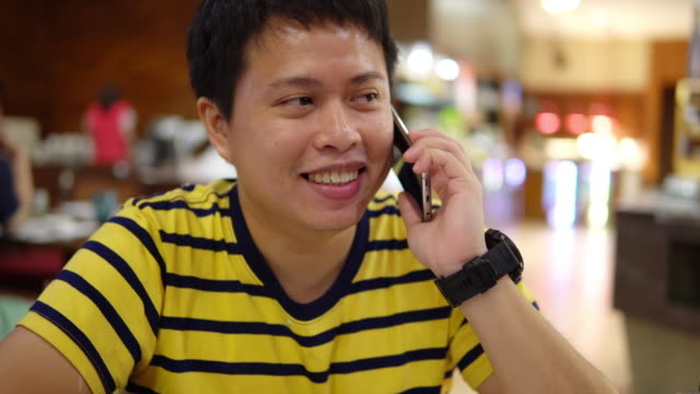 happy man talking on phone while waiting food in restaurant. - attending stock videos & royalty-free footage