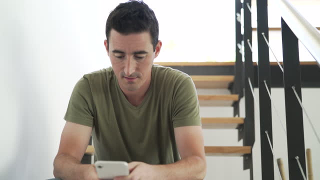 happy man using smart phone while sitting on staircase at home - 35 39 years stock videos & royalty-free footage
