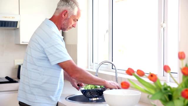 Glücklicher Mann Waschen Brokkoli im Waschbecken