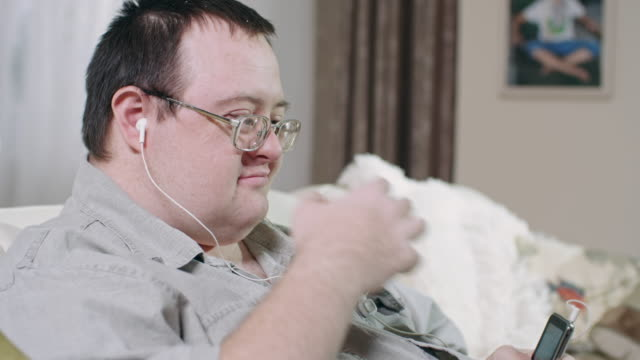 happy man with development disability enjoying music in earphones - nodding head to music stock videos and b-roll footage