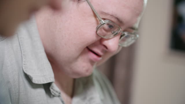 cu of happy man with down syndrome enjoying drawing - intellectual disability stock videos & royalty-free footage