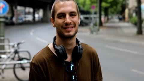 vídeos de stock e filmes b-roll de happy man with headphones and sunglasses in city - young men