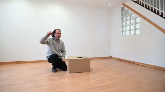 happy man with some keys in his hand and a cardboard box symbolizing a move. - only men stock videos & royalty-free footage
