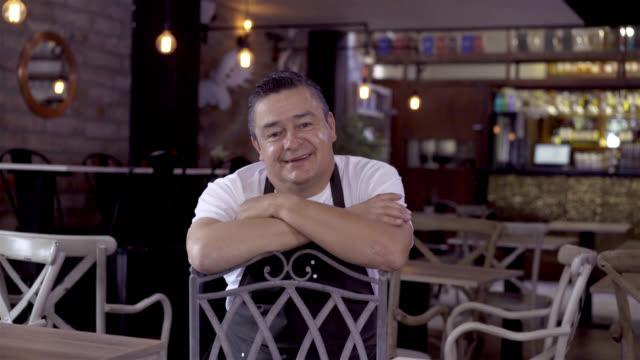 vídeos y material grabado en eventos de stock de feliz administrador de un restaurante mirando a la cámara sonriendo - américa del sur