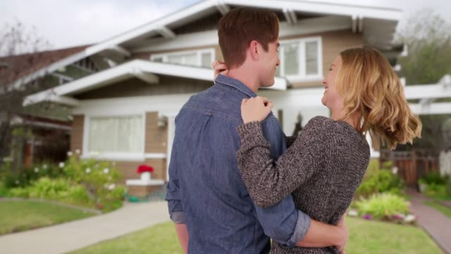 vidéos et rushes de happy married couple hugging and looking at newly purchase house from outside - jeunes mariés