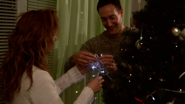 happy married couple putting lights on christmas tree - decorating the christmas tree stock videos & royalty-free footage