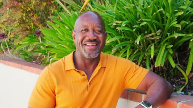 happy mature aged man in backyard - completamente calvo video stock e b–roll
