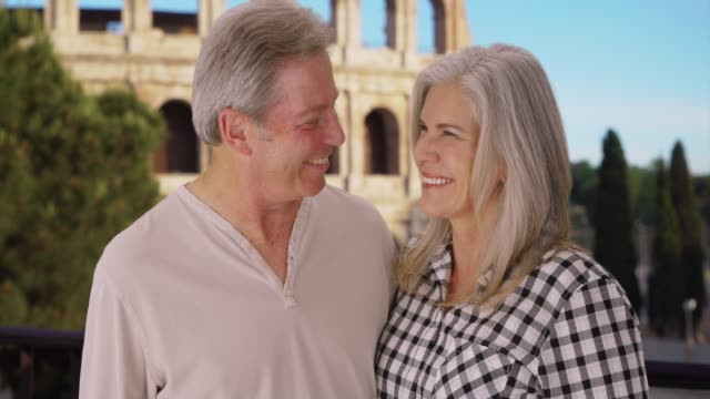happy mature caucasian couple smile happily in front of colosseum in rome - weitere themen stock-videos und b-roll-filmmaterial