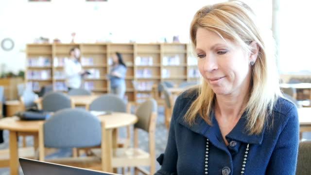 vídeos de stock, filmes e b-roll de madura mulher caucasiana feliz usando o laptop para bate-papo com vídeo ou estudar na biblioteca da faculdade - aluno mais velho