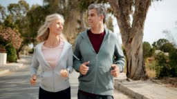 Happy mature couple jogging together on sunny day in spring