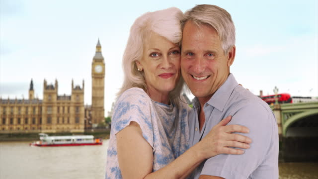 happy mature couple pose for a portrait in london - big ben点の映像素材/bロール