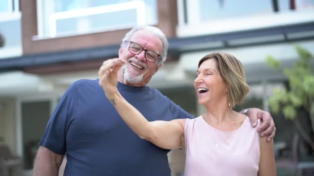 happy mature couple showing keys of their new house - davanti video stock e b–roll