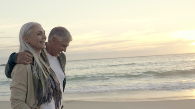 happy mature couple walking at beach during sunset - mature couple stock videos & royalty-free footage