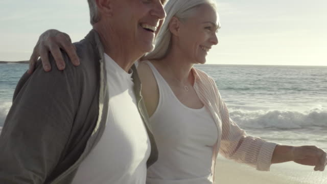 happy mature couple walking at beach in summer - mature couple stock videos & royalty-free footage