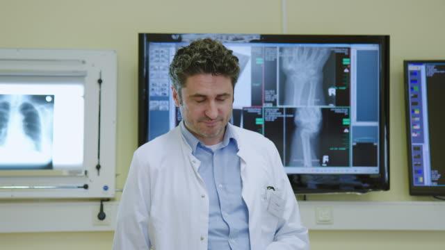 vidéos et rushes de docteur mûr heureux restant dans le bureau d'hôpital - chirurgien