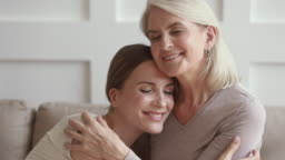 Happy mature mother embracing young daughter enjoy moments of tenderness