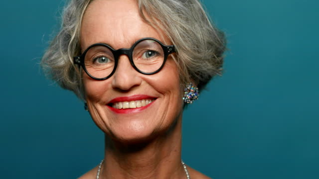 happy mature woman against blue background - spectacles stock videos & royalty-free footage