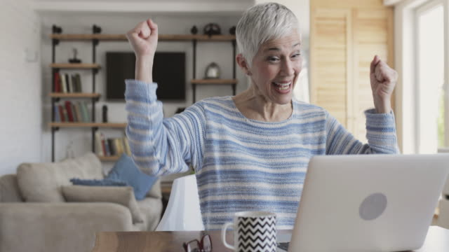 Happy mature woman celebrating while reading good new on the computer.