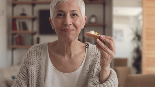 Happy mature woman having a breakfast at home and showing thumbs up while looking at camera.