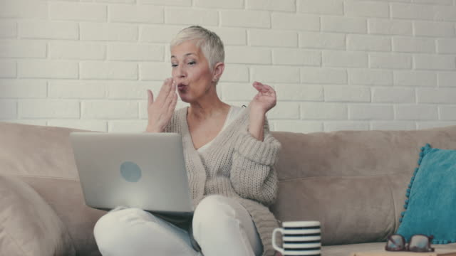 happy mature woman sending kisses and waving while having video chat over laptop. - surfing the net stock videos & royalty-free footage