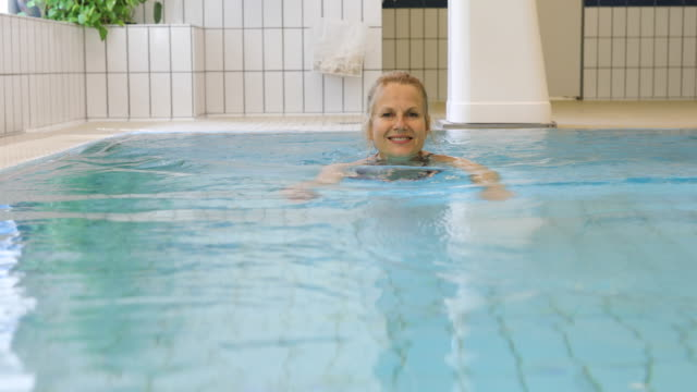 Happy mature woman swimming in pool at gym