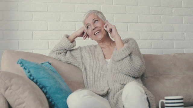 happy mature woman talking to someone over mobile phone while relaxing on the sofa. - senior women stock videos & royalty-free footage
