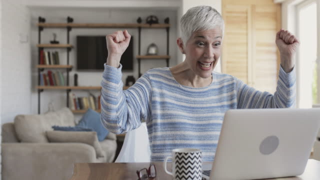 happy mature woman using laptop and celebrating good news. - good news stock videos & royalty-free footage