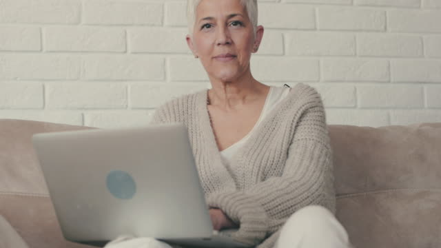 Happy mature woman using laptop on the sofa and looking at camera.