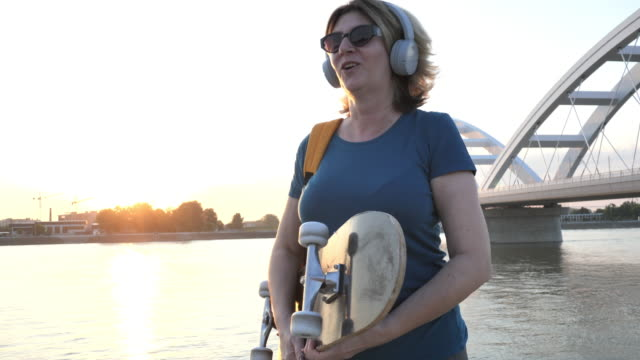 glad mogen kvinna med skateboard utomhus på sommaren - medelålders kvinnor bildbanksvideor och videomaterial från bakom kulisserna