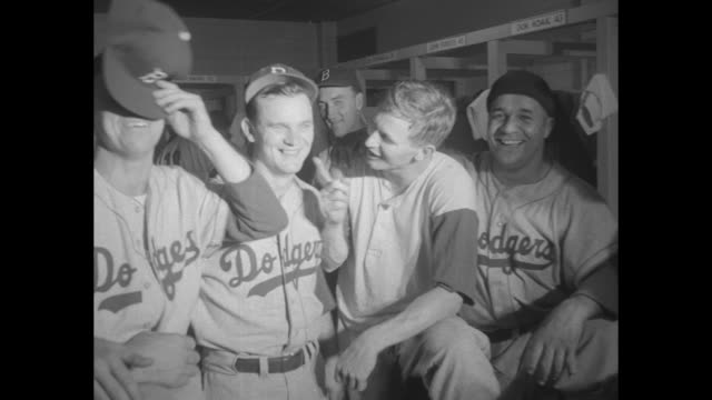 WS happy members of the Brooklyn Dodgers baseball team celebrate in dressing room at Milwaukee's County Stadium after clinching the National League...