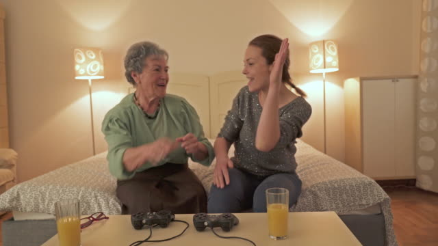 Happy mid adult woman and her mother playing video games giving high-five to each other.