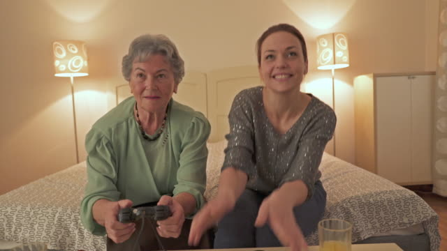 happy mid adult woman and her senior mother playing video games at home. - senior women stock videos & royalty-free footage