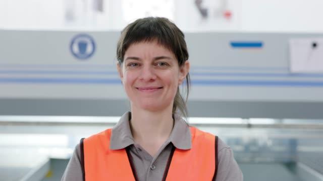 happy mid adult woman in warehouse - caposquadra video stock e b–roll
