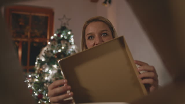 ms happy mid adult woman opening her christmas present - low lighting stock videos & royalty-free footage